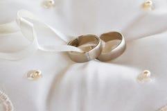 Deux anneaux de mariage d'or sur un oreiller Photographie stock