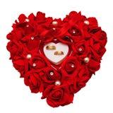 Deux anneaux de mariage d'or sur un oreiller décoratif des roses rouges Image stock
