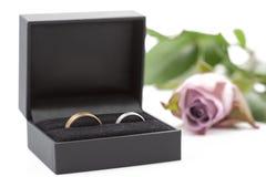 Deux anneaux de mariage dans une boîte à bijoux sur le blanc Photos stock