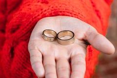 Deux anneaux de mariage dans une main de la jeune mariée Photo stock