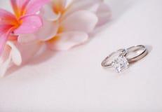 Deux anneaux de mariage devant les fleurs tropicales Photo stock