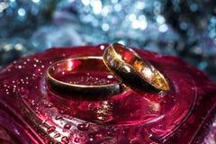 Deux anneaux de mariage de différentes tailles faites en or sur le cristal rouge photographie stock libre de droits
