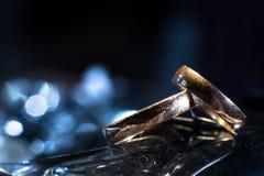 Deux anneaux de mariage de différentes tailles faites en or sur le fond bleu de bokeh photos stock