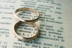 Deux anneaux de mariage distincts à côté du ` de mot divorcent le ` Photographie stock libre de droits