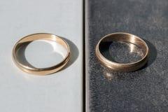 Deux anneaux de mariage distincts sur un fond noir et blanc Concentré Images stock