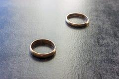 Deux anneaux de mariage distincts sur un fond noir Le concept o Images stock