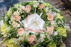 Deux anneaux de mariage parmi les fleurs Photos libres de droits