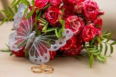 Deux anneaux de mariage, roses rouges Papillon d'Arsenie Photographie stock libre de droits