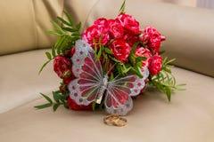 Deux anneaux de mariage, roses rouges Papillon d'Arsenie Photo libre de droits