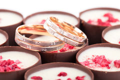 Deux anneaux de mariage sur des chocolats avec des framboises Photo libre de droits