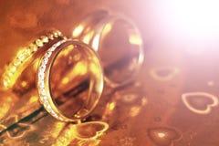 Deux anneaux de mariage sur un fond, un éclat et une réflexion d'or Photographie stock libre de droits