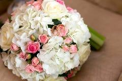 Deux anneaux de mariage à un bouquet des roses rouges et blanches Images libres de droits