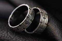 Deux anneaux des hommes avec le traitement différent sur un support fait de cuir noir photographie stock