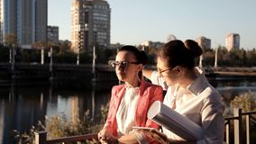 Deux architectes de filles se tiennent prêt la rivière et discutent le projet de construction Affaires, construction banque de vidéos