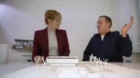Deux architectes donnant haut cinq derrière un housemodèledans le bureau banque de vidéos