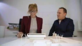 Deux architectes donnant haut cinq derrière un housemodèledans le bureau clips vidéos