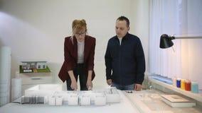Deux architectes regardant la projection augmentée de réalité de la maison sur le bureau clips vidéos