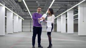 Deux architectes regardent un modèle, le tenant dans des mains, et discutent un projet clips vidéos