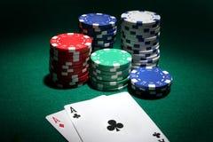 Deux as et piles de casino ébrèche dedans le fond Image libre de droits