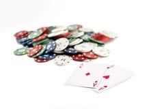 Deux as et piles de casino ébrèche dedans le fond Photo stock