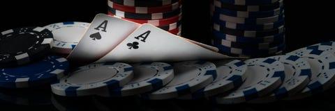 Deux as noirs sur des cartes de tisonnier rougeoient dans un casino foncé Photographie stock libre de droits