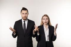 Deux associés dans les costumes noirs, l'homme barbu bel et belle la femme blonde choqués ne savent pas quoi faire image stock