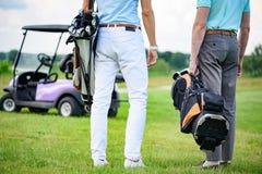 Deux associés de jeu se tenant sur le terrain de golf Image libre de droits