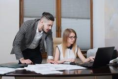 Deux associés discutent des plans ou des idées se reposant au bureau et travaillant sur l'ordinateur portable photographie stock