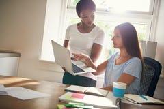 Deux associés féminins travaillant sur un ordinateur portable Photos stock