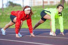 Deux athlètes caucasiens se tenant préparés au fonctionnement sur le cours de voie photo libre de droits
