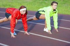 Deux athlètes caucasiens se tenant préparés au fonctionnement sur le cours de voie images libres de droits