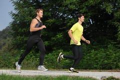 Fonctionnement de deux athlètes d'hommes/pulsant Image libre de droits