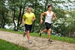 Fonctionnement de deux athlètes d'hommes/pulsant Photos stock