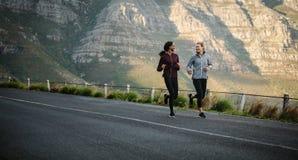 Deux athlètes de femmes courant sur la route Photos libres de droits