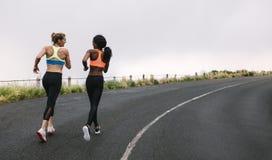Deux athlètes de femmes courant sur la route Image libre de droits