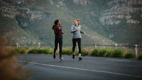 Deux athlètes de femmes courant sur la route Photographie stock