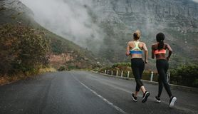 Deux athlètes de femmes courant sur la route Image stock