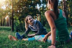 Deux athlètes féminins gais réchauffant avant exercice s'étendant faisant s'exerçant pour des jambes se reposant sur l'herbe Image stock