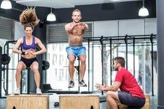 Deux athlètes musculaires faisant des postures accroupies sautantes Images stock