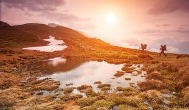 Deux augmentant dans les montagnes dans le beau matin à un petit lac Image libre de droits