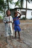 Deux aux pieds nus, huit ans, garçon à la peau foncée, se tenant dans la route du Photographie stock libre de droits