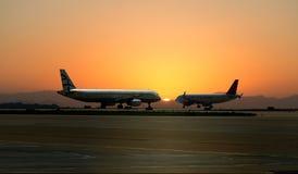 Deux avions sur le fond du coucher du soleil à l'aéroport en Attica Greece, avril 2015 Photos stock