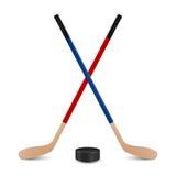 Deux bâtons de hockey et galets croisés illustration libre de droits
