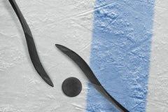 Deux bâtons de hockey, un galet et un fragment de l'arène de glace avec a Images libres de droits