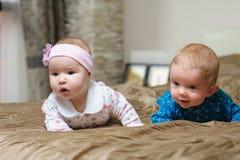 Deux bébés se trouvant sur le ventre et grimaçant photographie stock
