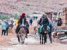 Deux bédouins montent des ânes et parlent entre eux dans PETRA près de la ville de Wadi Musa en Jordanie image stock
