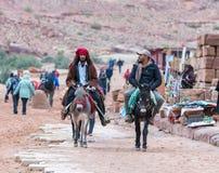 Deux bédouins montent des ânes et parlent entre eux dans PETRA près de la ville de Wadi Musa en Jordanie photographie stock