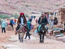 Deux bédouins montent des ânes et parlent entre eux dans PETRA près de la ville de Wadi Musa en Jordanie image libre de droits