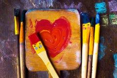 Deux baisers de brosses de sourire au-dessus de palette avec le symbole de foyer Photographie stock libre de droits