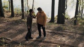 Deux balades d'amis d'hommes sur le sentier piéton en bois et débuts discutant le jour ensoleillé banque de vidéos